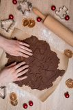 Tagliando i biscotti di Natale, uomini di pan di zenzero bollenti, facenti Cristo fotografia stock libera da diritti