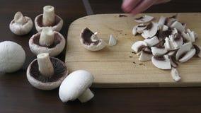 Tagliando i funghi a pezzi sbucciati e bianchi stock footage
