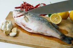 Tagliando il pesce per la spigola cuocia a vapore con il limone, l'aglio ed il peperoncino rosso Fotografie Stock