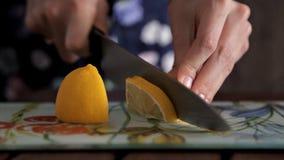 Tagliando limone su un bordo per la preparazione del succo di frutta fresco ed aromatico video d archivio