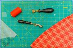 Tagliando panno di tela su una stuoia, facente tessuto fotografia stock libera da diritti