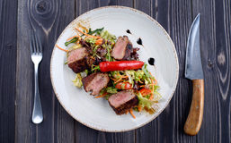Tagliata of beef with salad on a plate Stock Image