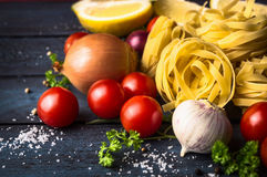 Tagliatelle干面团用蕃茄和香料在蓝色木背景 免版税库存照片