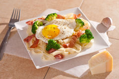 Tagliatelle面团用硬花甘蓝、熏火腿和煎蛋 免版税库存照片