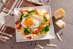 Tagliatelle面团用硬花甘蓝、熏火腿和煎蛋 库存图片