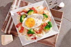 Tagliatelle面团用硬花甘蓝、熏火腿和煎蛋 免版税库存图片