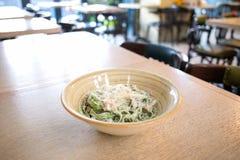 Tagliatelle面团用菠菜、蘑菇和帕尔马干酪在板材在餐馆 免版税库存照片