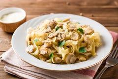 Tagliatelle面团用蘑菇、荷兰芹和帕尔马干酪在木桌上 库存照片