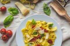 Tagliatelle в итальянских цветах, зажаренных в духовке томатах, базилике Tagliatelle Стоковое Фото