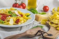 Tagliatelle в итальянских цветах, зажаренных в духовке томатах, базилике Tagliatelle Стоковое фото RF