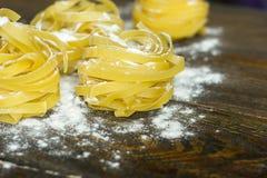 Tagliatelle макаронных изделий с мукой на таблице, clous-up стоковое фото