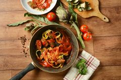 Tagliatelle with artichoke and tomato sauce in the pan with ingr Stock Photography