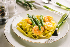 Tagliatelle with asparagus and prawns. Tagliatelle with cream of green asparagus and prawns Stock Images