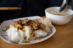 Tagliatelle bianche del riso casalingo con il pollo arrostito e l'aglio sulla t fotografie stock