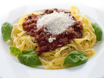 Tagliatelle bolognese. Decorated with some basil leafs and covered with parmesan Royalty Free Stock Photography