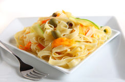 Tagliatelle bowl. A plate of tagliatelle with ribbons of carrot and courgette, stuffed olives and a sprinkling of black pepper,  tossed in a garlic flavoured Stock Photo