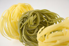 Tagliatelle bunches. Coloured tagliatelle on the white background royalty free stock image