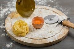Tagliatelle casalinghe crude italiane della pasta alla tavola concreta fotografia stock