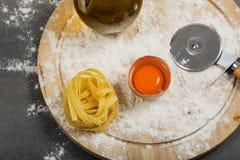 Tagliatelle casalinghe crude italiane della pasta alla tavola concreta immagini stock