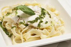Tagliatelle with cheese sauce. Tagliatelle pasta with cheese sauce and pesto Stock Photography