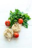 Tagliatelle con gli ingredienti per la cottura della pasta Prezzemolo riccio, aglio, pomodori su una tavola di legno Fotografia Stock