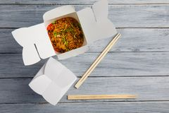 Tagliatelle con le verdure in una scatola per l'esportazione su una tavola di legno fotografie stock