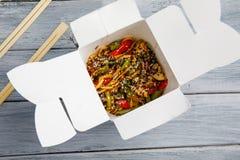 Tagliatelle con le verdure in una scatola per l'esportazione su una tavola di legno immagini stock libere da diritti