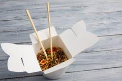 Tagliatelle con le verdure in una scatola per l'esportazione su una tavola di legno fotografia stock libera da diritti
