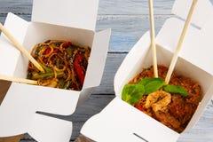 Tagliatelle con le verdure in una scatola per l'esportazione su una tavola di legno fotografia stock