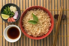 Tagliatelle con salsa e l'ingrediente backgr di legno/di bambù Immagine Stock