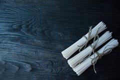 Tagliatelle crude del udon in rotoli su un fondo di legno scuro Posto per testo Vista da sopra fotografie stock