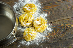 Tagliatelle da massa com farinha na tabela e na bandeja, clous-up Fotografia de Stock Royalty Free