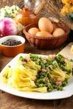 Tagliatelle della pasta con i piselli e la pancetta affumicata Fotografia Stock