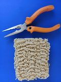Tagliatelle di ramen accanto alle pinze - concetto per riparare qualche cosa facendo uso delle tagliatelle - fondo blu fotografia stock