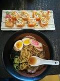Tagliatelle di ramen, uova in ciotola e rotoli di sushi Fotografie Stock