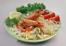 Tagliatelle di riso con i gamberetti reali su un piatto verde chiaro con le cipolle tagliate fotografie stock