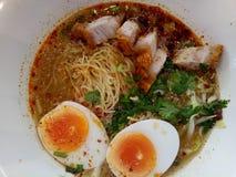 Tagliatelle di Tom Yum con gli uova sode e la carne di maiale croccante fotografie stock