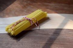 Tagliatelle di vermicelli crude legate con corda su un tagliere di legno Immagini Stock Libere da Diritti
