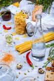 Tagliatelle, fusilli e una bottiglia di acqua Un primo piano della composizione della cena su un fondo di pietra grigio Italiano  Fotografia Stock Libera da Diritti