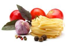 Tagliatelle, garlic, tomatoes, spices, basil. Stock Photo
