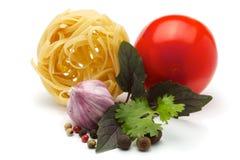 Tagliatelle, garlic, tomatoes, spices, basil, pars Stock Photos