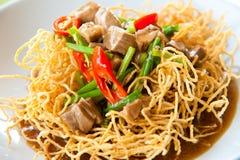 Tagliatelle gialle fritte nel grasso bollente di stile cinese con porco Immagini Stock