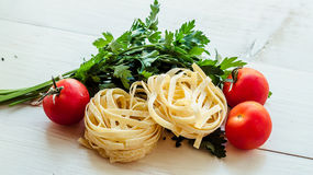 Tagliatelle with ingredients for cooking pasta. Curly parsley, garlic, tomatoes on a wooden table. Royalty Free Stock Photo