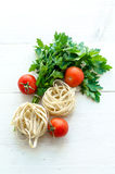 Tagliatelle with ingredients for cooking pasta. Curly parsley, garlic, tomatoes on a wooden table. Stock Photo