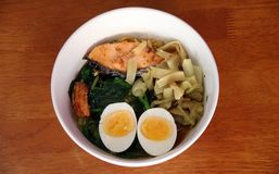 Tagliatelle istantanee bollite con l'uovo sodo, la carne di pesce, i legumi verdi e la lattuga del sottaceto nella ciotola bianca fotografia stock