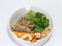 Tagliatelle istantanee bollite con lo strappo della carne di maiale, l'uovo fritto, la carne di pesce e la verdura verde nella ci fotografia stock