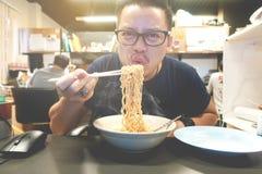 Tagliatelle istantanee mangiarici di uomini asiatiche molto calde e piccanti immagini stock