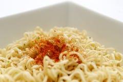 Tagliatelle istanti con la polvere di peperoncino rosso sulla parte superiore Fotografia Stock