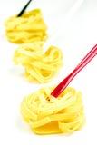 Tagliatelle italiane crude su un fondo bianco Immagini Stock