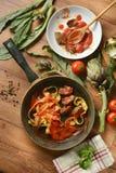 Tagliatelle med kronärtskocka- och tomatsås i pannan med ingr fotografering för bildbyråer